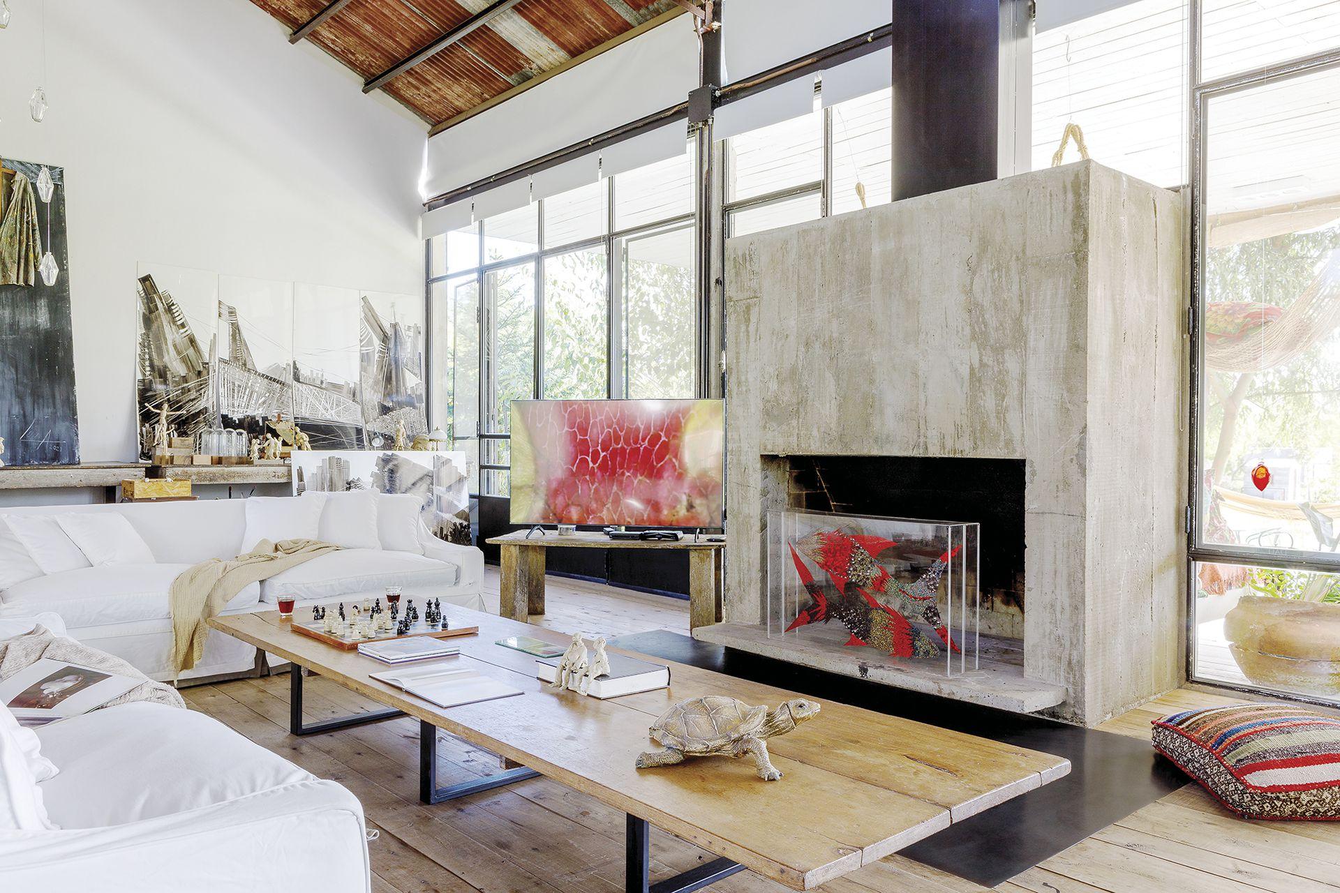 El living ocupa el espacio central frente al hogar de hormigón que, cuando no se usa, les da marco a las obras de Berna, como la caja de acrílico con peces que se ve en esta imagen.