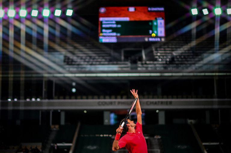 Iluminado pero desolado, el estadio Philippe Chatrier es testigo de un saque de Federer en una sesión sin público a raíz del toque de queda que rige a la noche en París.