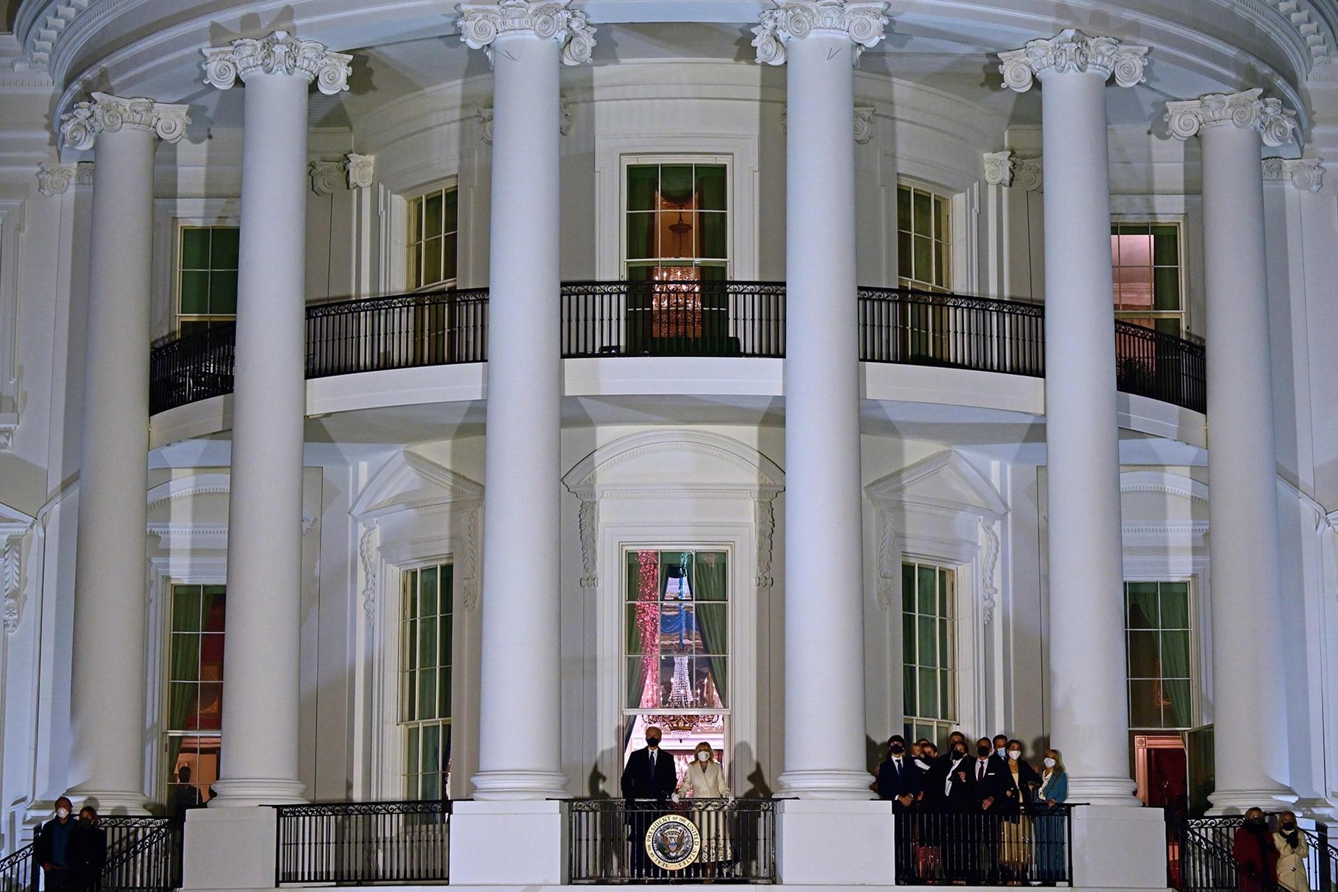 El presidente estadounidense Joe Biden (CL) y la primera dama Jill Biden (CR) aparecen en el balcón de la habitación azul mientras ellos y sus familiares (derecha) ven los fuegos artificiales desde la Casa Blanca en Washington