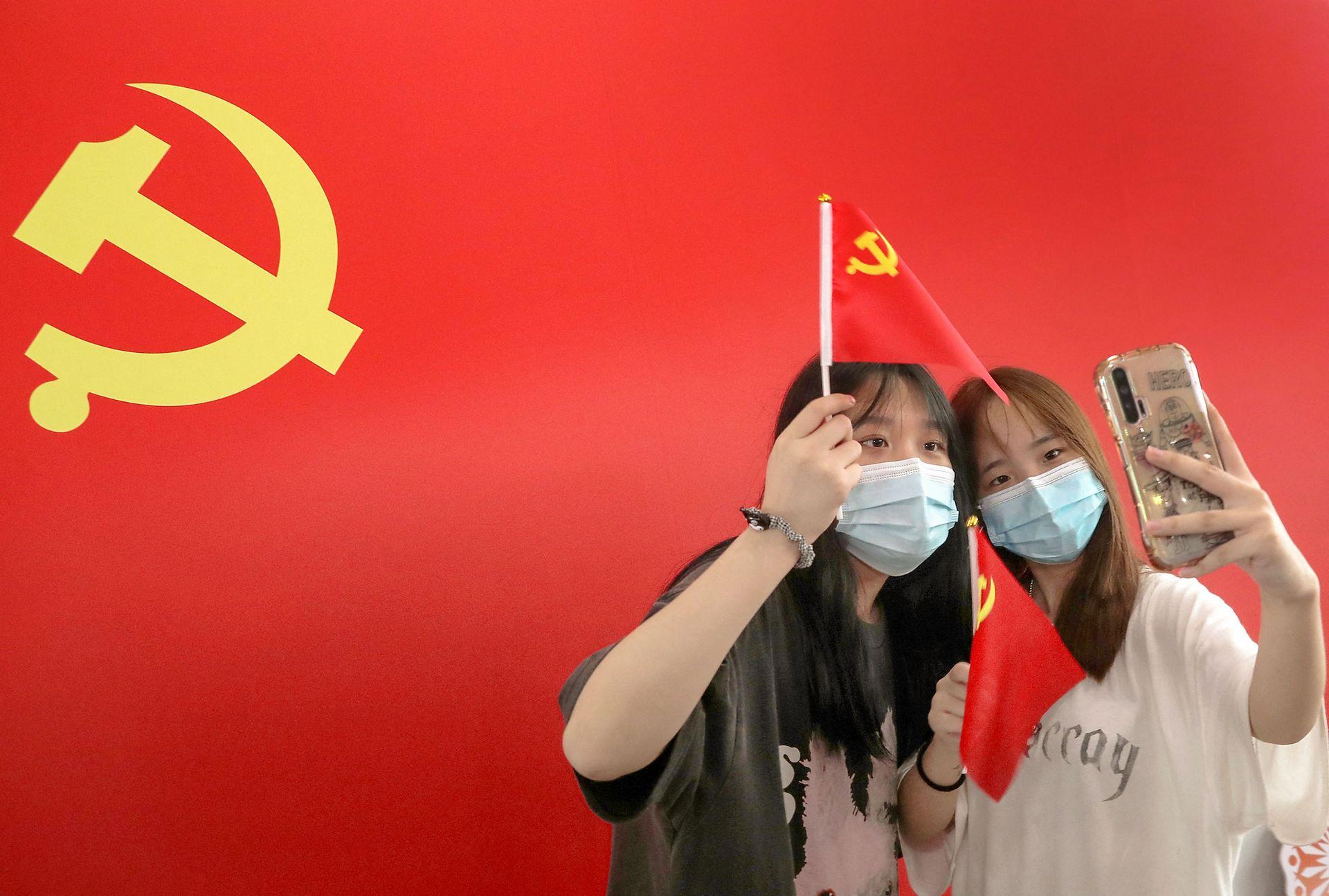 Dos jóves se toman una selfie con la bandera de fondo