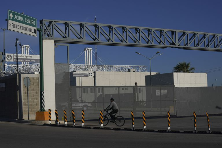 Un hombre en bicicleta frente a la entrada cerrada de un puente fronterizo internacional que conecta a las ciudades de Del Río, Texas, y Ciudad Acuña, México, el viernes 24 de septiembre de 2021. (AP Foto/Fernando Llano)