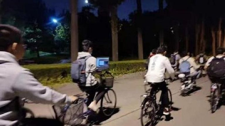 En una de las fotos, un estudiante de la Universidad Tsinghua utilizaba su computador portátil mientras montaba en bicicleta