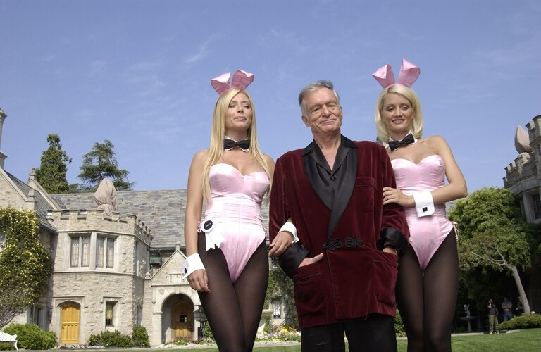 Kendra Wilkinson y Holly Madison junto a Hugh Hefner, con la mansión Playboy de fondo (Getty)