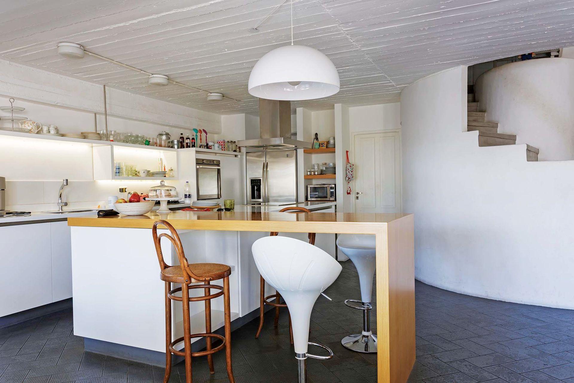 Junto a la barra, mix de banquetas: antiguas de madera con esterilla y modernas 'Candy' en blanco (Falabella).