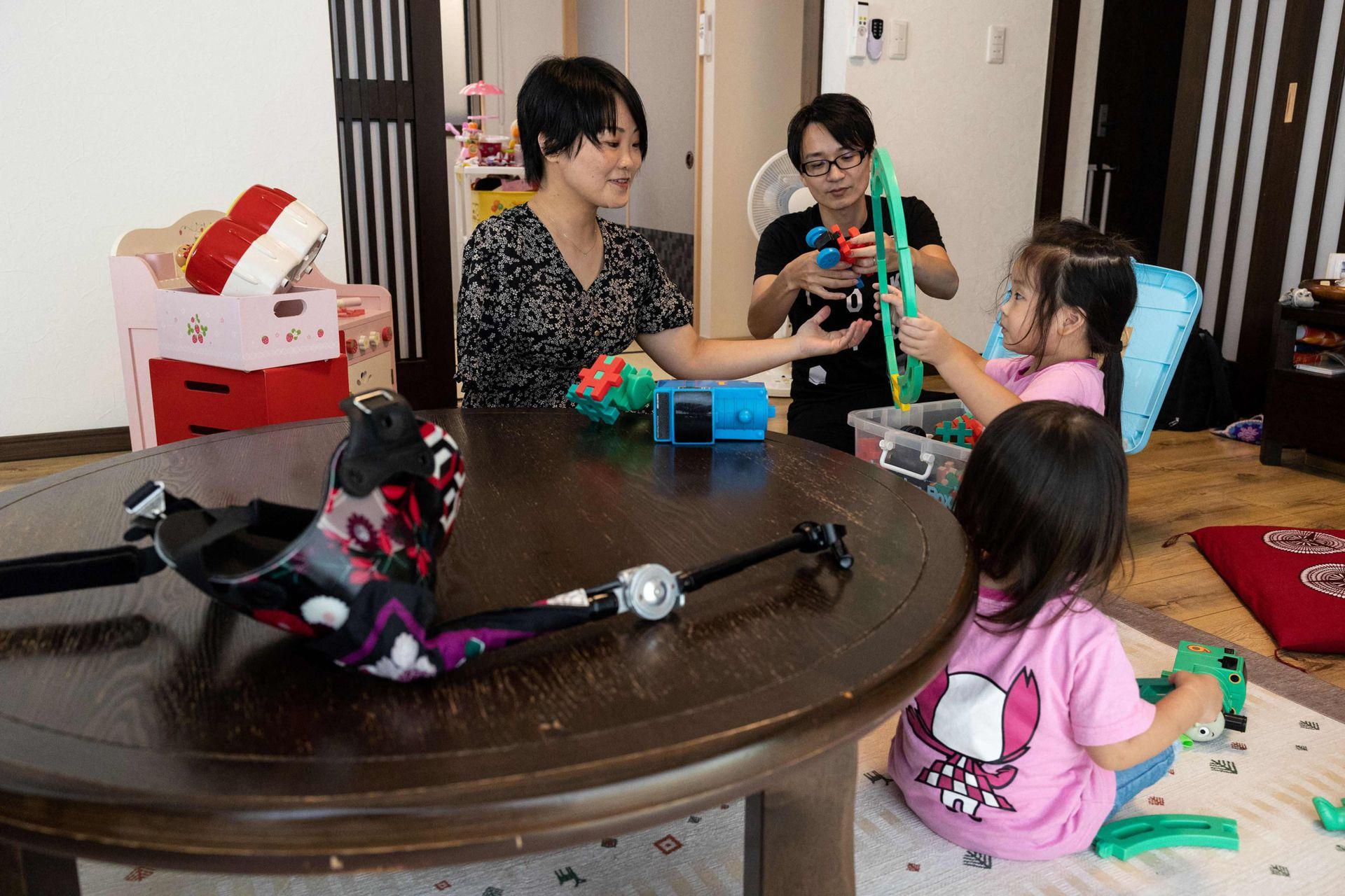 La violinista japonesa Manami Ito con sus hijas Miu y Mei y su esposo Yuki. Se ve el brazo protésico sobre la mesa en su residencia en Shizuoka