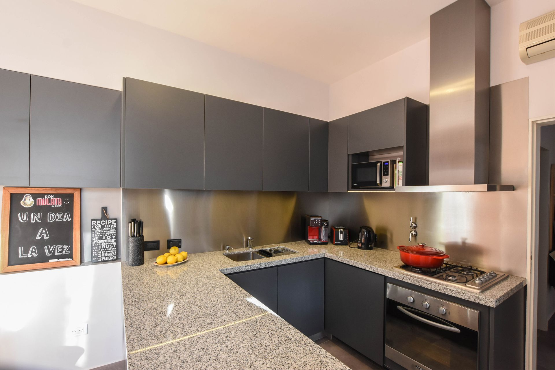 Alacena y muebles bajomesada de melamina gris grafito (Faplac), alzada de acero inoxidable, mesada 'Gris mara' (todo diseño de Estudio MPB).