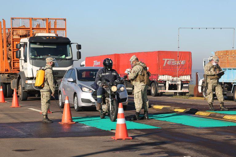 Militares controlando a conductores de vehículos en puesto de control de aduana en la frontera con Brasil