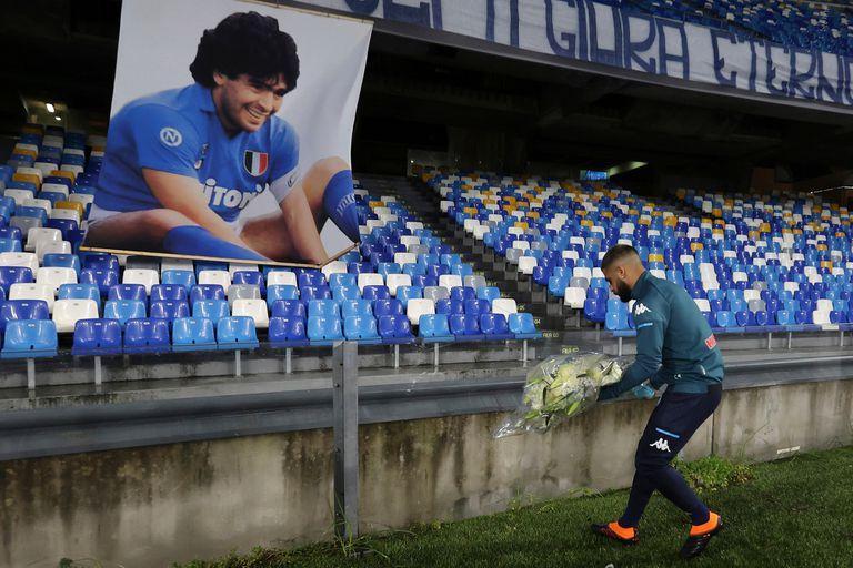 Lorenzo Insigne, capitán de el Napoli, deposita un ramo de flores frente a una imagen de Diego Armando Maradona en el San Paolo