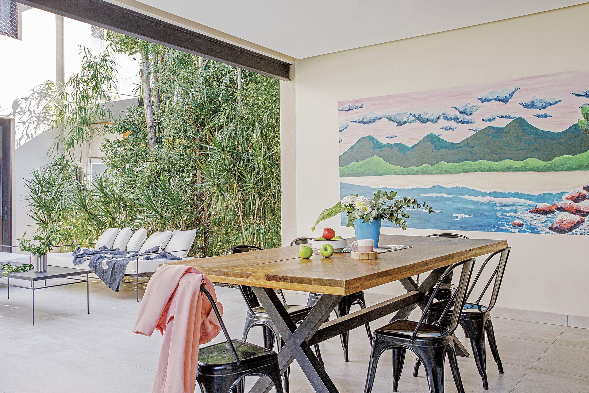 Mesa de lapacho (Crudo Home) rodeada de sillas 'Tólix'. Mural realizado por Michel Fassi (Eileen Vergez, asesoramiento de arte).