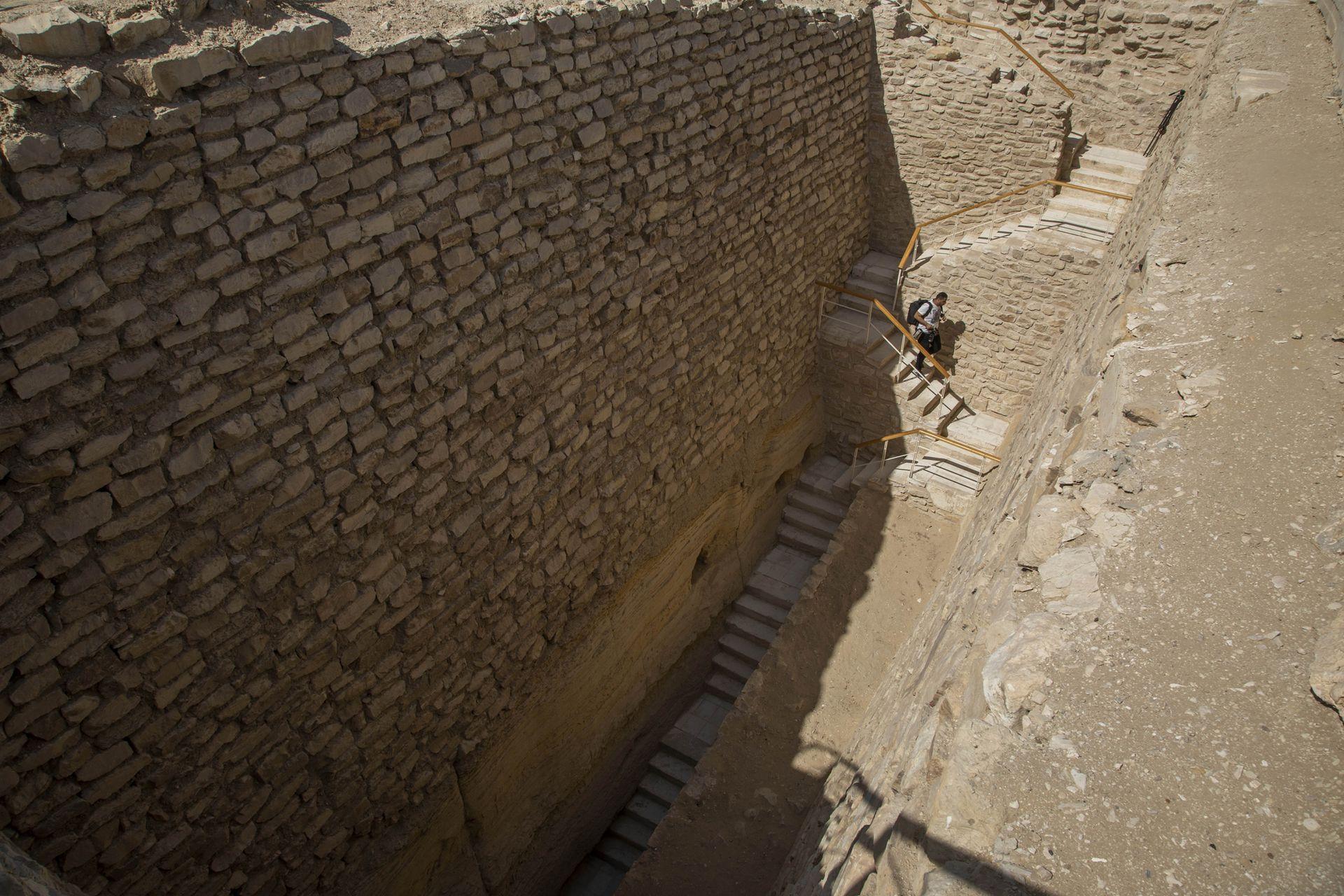 Un periodista baja las escaleras hacia el cementerio sur del rey Djoser, para filmarlo después de su restauración