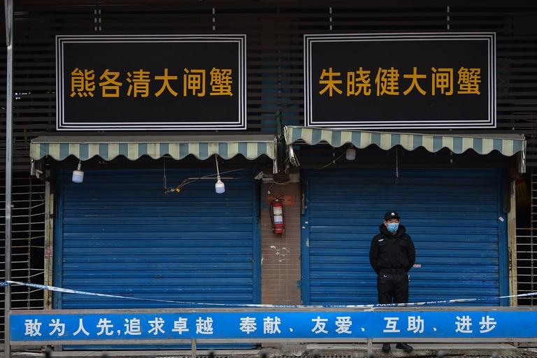 En esta foto de archivo tomada el 24 de enero de 2020, un guardia de seguridad se encuentra frente al mercado mayorista de mariscos de Huanan, donde se detectó el coronavirus por primera vez en Wuhan