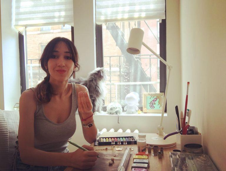 Micaela Gallino, de 31 años, mientras trabaja sobre las joyas de arcilla polimérica. Detrás, su gato Miguel