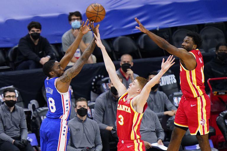 Shake Milton de los 76ers de Filadelfia lanza el balón superando a Kevin Huerter y Solomon Hill en el juego 2 de las semifinales de la Conferencia Este el martes 8 de junio del 2021. (AP Photo/Matt Slocum)