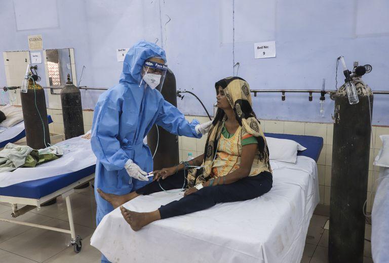 Una enfermera atiende a una paciente en un centro gratuito par enfermos de COVID-19 operado por una ONG a las afueras de Nueva Delhi, India