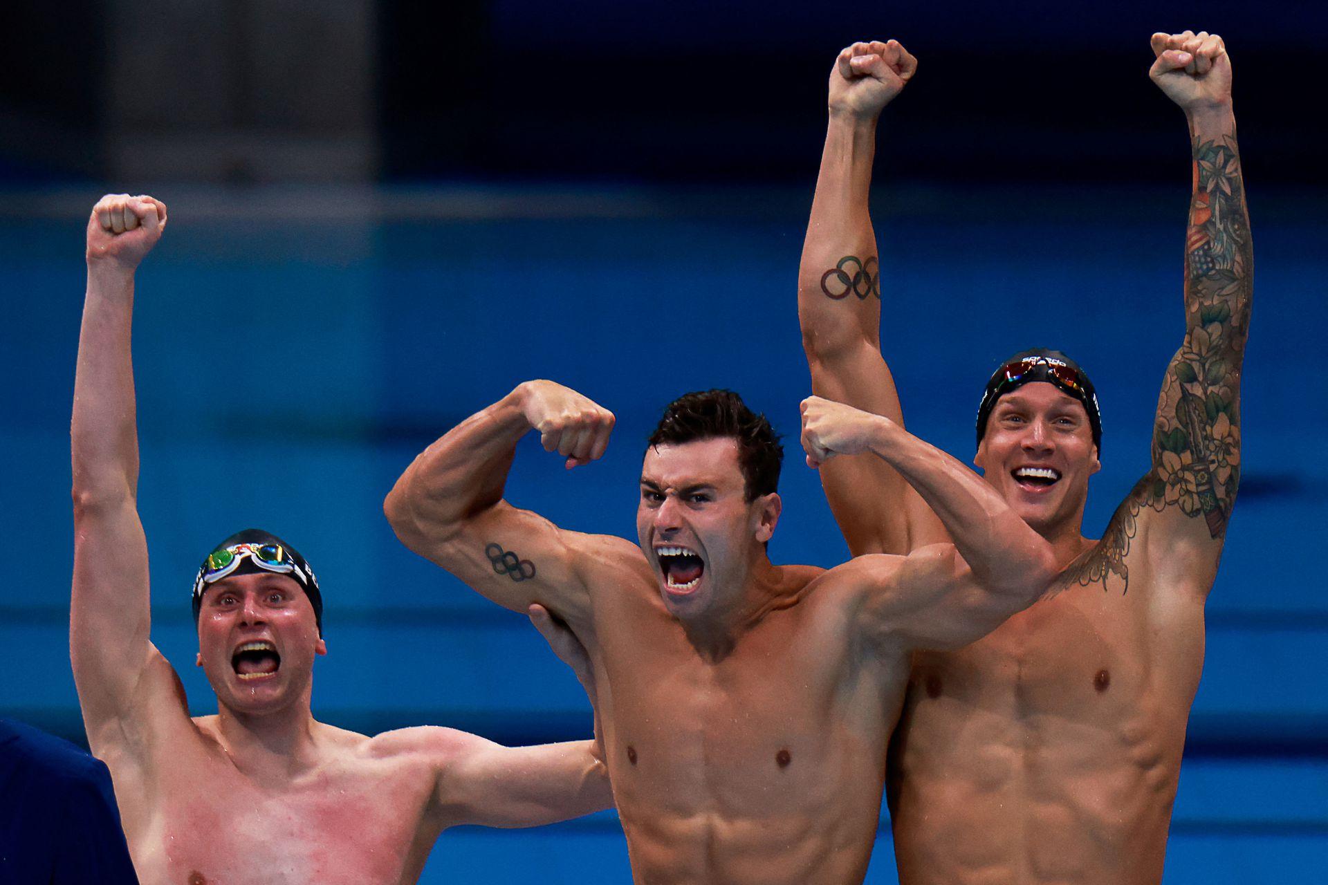 Caeleb Dressel (R) de EE. UU., Blake Pieroni (C) de EE. UU. Y Bowen Becker de EE. UU. Celebran su victoria para llevarse el oro en la final del evento masculino de natación de relevos 4x100m estilo libre durante los Juegos Olímpicos de Tokio 2020 en el Centro Acuático de Tokio en Tokio el 26 de julio , 2021.