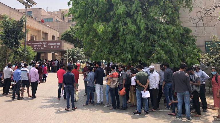 Gente esperando una prueba de covid frente a un hospital administrado por el gobierno en Noida