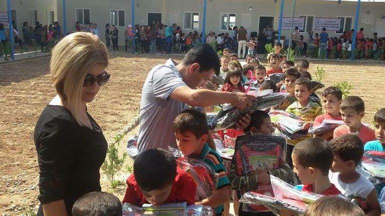 Tima y Abdullah reparten ropa comprada por la Fundación en un campo de refugiados en Irak