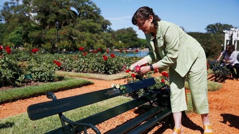 """Laura Carrizo, coloca flores en el banco con la placa de Gustavo Eduardo Codinal. """"Era mi amigo del alma"""", dijo"""