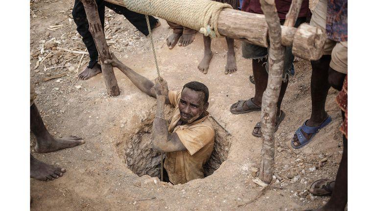Un minero surge del agujero de la mina informal de zafiro