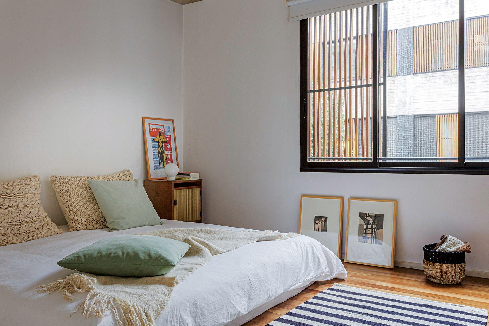 En el dormitorio principal, manta de lana sobre la cama, almohadones y alfombra a rayas blancas y negras (Elementos Argentinos). Los cuadros son del artista brasileño Sergio Fingermann, tío de Tamar.