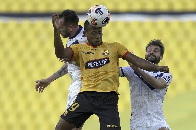 El ecuatoriano Luis Fernando León (C) pelea por el balón con Federico Mancuello y Agustín Bouzat