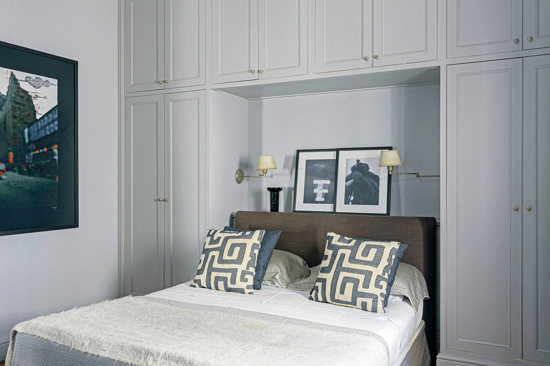 El cuarto de huéspedes se trabajó en grises y azules. Se armó un ropero donde empotrar la cama, con estante de apoyo detrás de la cabecera tapizada en lino (De Levie).