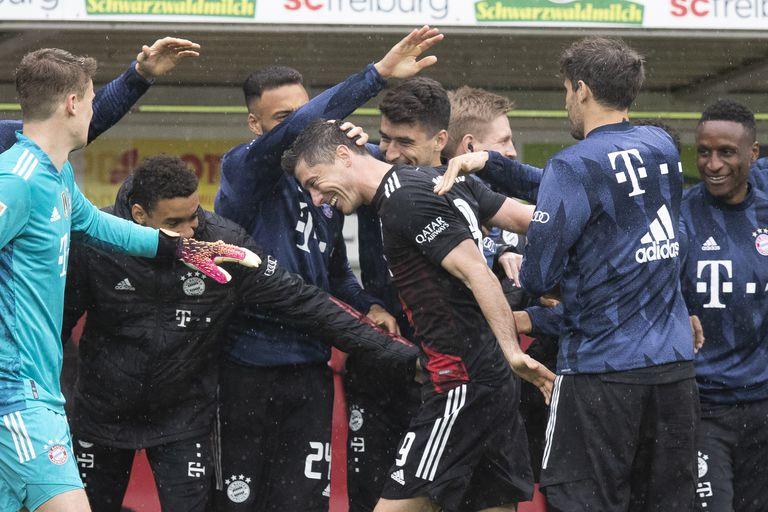 Robert Lewandowski, centro, festeja con sus compañeros del Bayern Munich su gol contra Freiburg que le permitió igualar el récord de Gerd Müller de 40 goles en la temporada, que se remontaba a 1972. En Freiburg, Alemania, sábado 15 de febrero de 2021. (Tom Weller/dpa via AP)