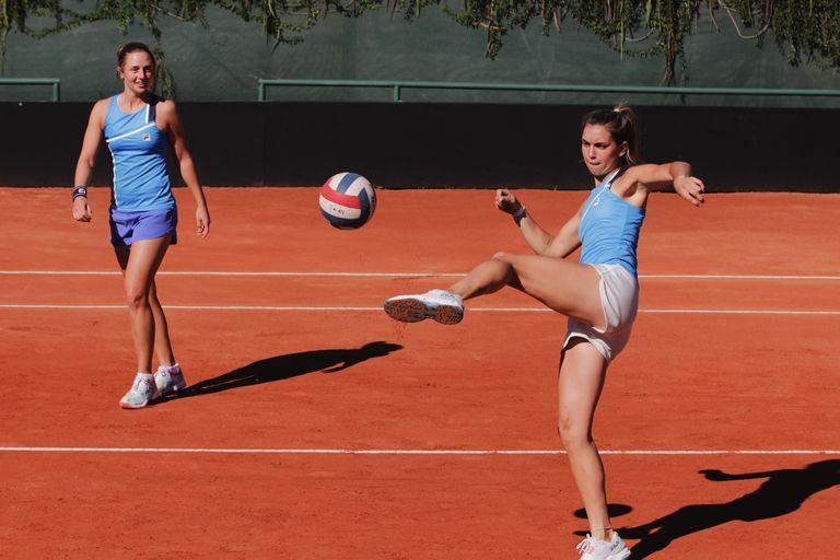 Un momento de fútbol-tenis y risas en el equipo argentino de la Billie Jean King Cup: patea Guillermina Naya ante la mirada de Nadia Podoroska.