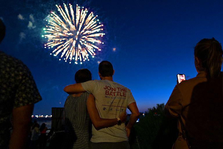 La gente observa cómo los fuegos artificiales estallan sobre el puerto de Nueva York para celebrar el fin de las restricciones