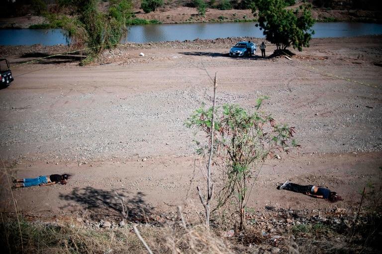 Los cadáveres de dos hombres asesinados en una disputa entre carteles yacen en un paraje de Sinaloa