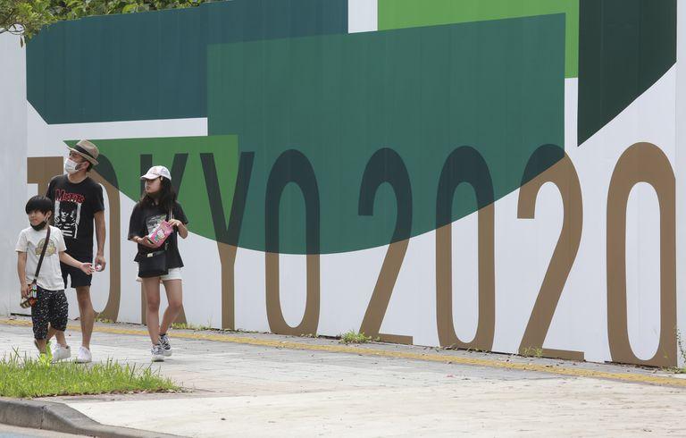 Tres personas pasan junto a carteles de promoción de los Juegos Olímpicos de Tokio.