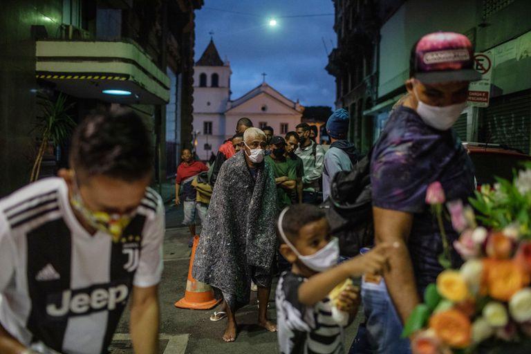 Una fila de indigentes aguarda su turno para recibir sándwiches y sopa de caridad en la ciudad de San Pablo