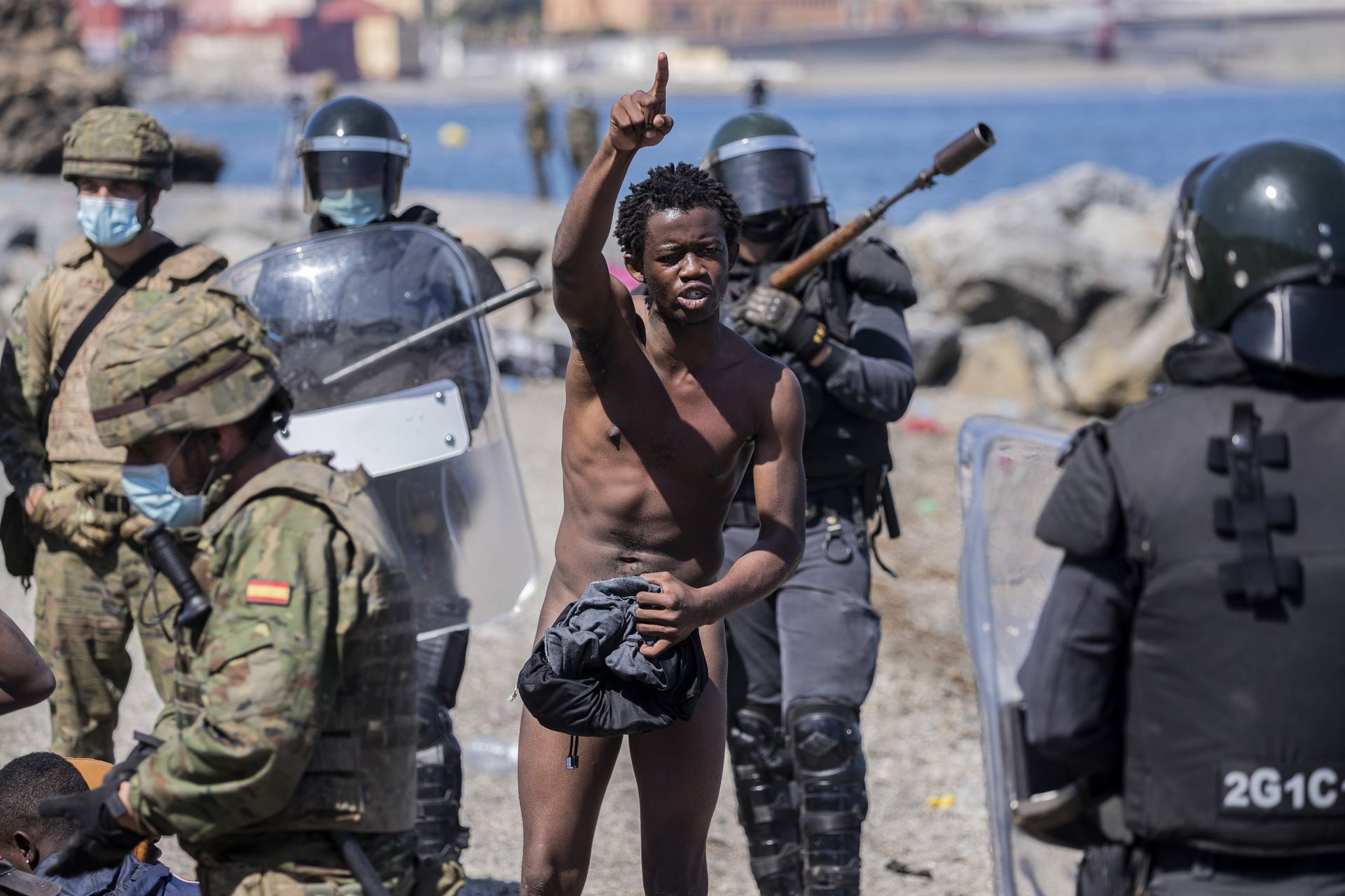 Un migrante totalmente desnudo, discute con las fuerzas de seguridad españolas, momentos antes de ser expulsado a Marruecos en el enclave español de Ceuta