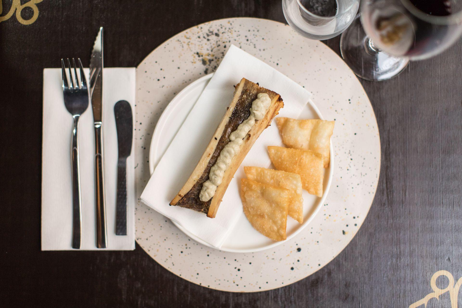 Médula de llama rostizada con puré de berenjenas asadas y chips crocantes.