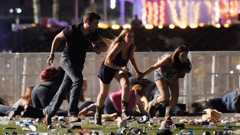 Tres asistentes al festival de música country en Las Vegas intentan refugiarse de la lluvia de balas disparadas por un tirador desde el hotel Mandalay Bay