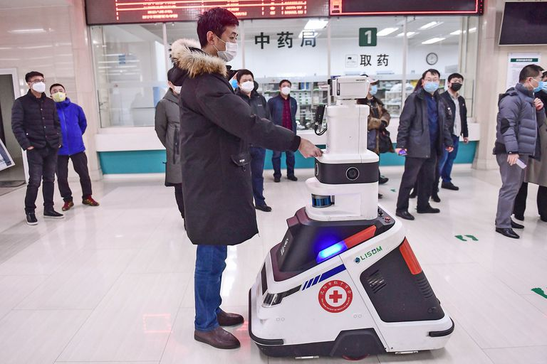 Un robot que toma temperaturas y desinfecta personas recorre los pasillos de un hospital en Shenyang, China.