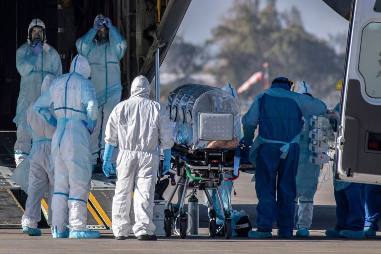 Los trabajadores de la salud trasladan a un paciente infectado con COVID-19 a un Hércules C-130, para llevarlo a la ciudad de Concepción, en una base de la Fuerza Aérea de Chile en Santiago, Chile, el 24 de mayo de 2020