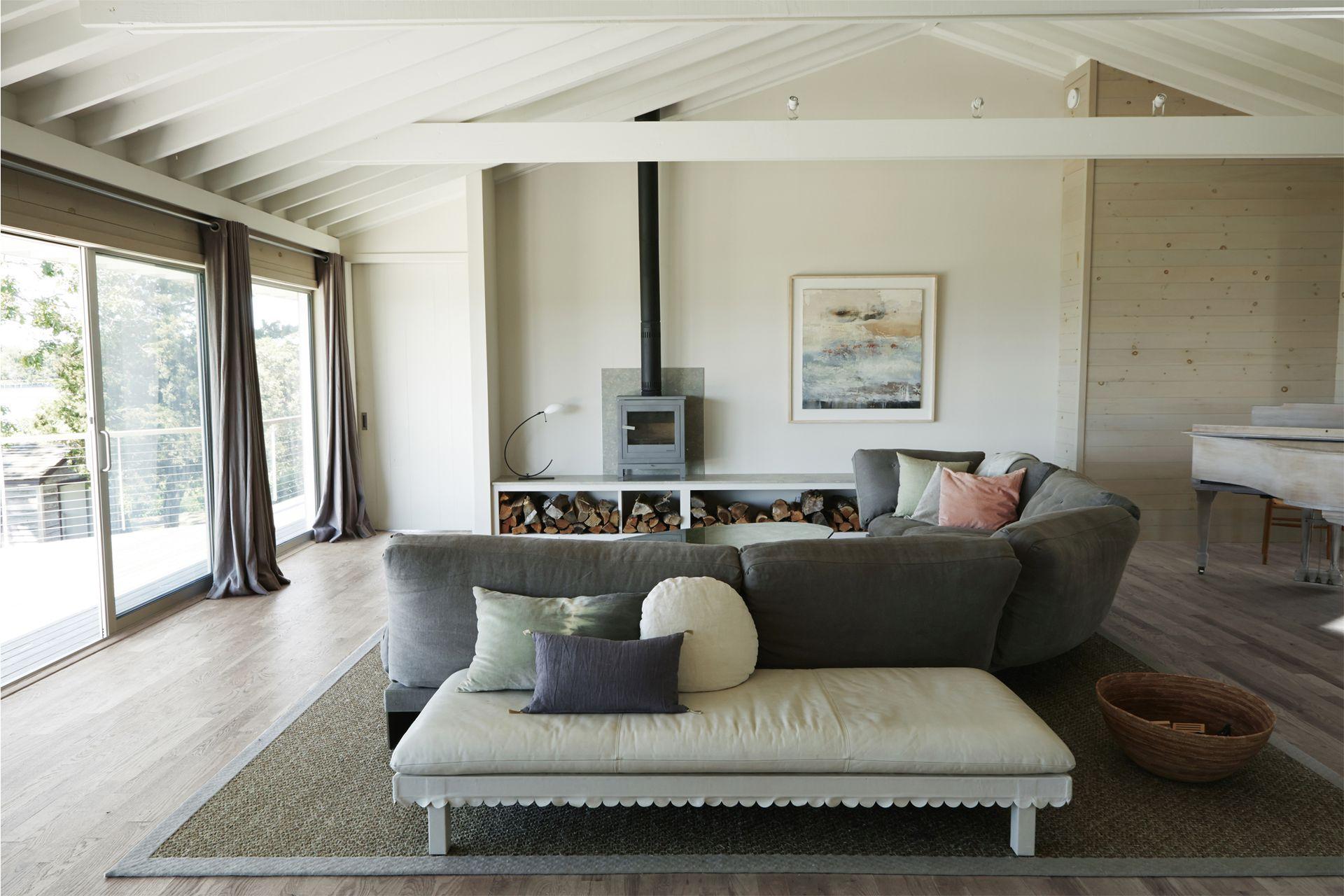 """Alfombra de fibras naturales con bordes de cuero. El sofá 'Eternal Dreamer' (Ochre) define el living y comparte el color de las cortinas. Sobre el mueble y con respaldo de chapa, pequeña salamandra """"de mesa"""" (Chesney's)."""