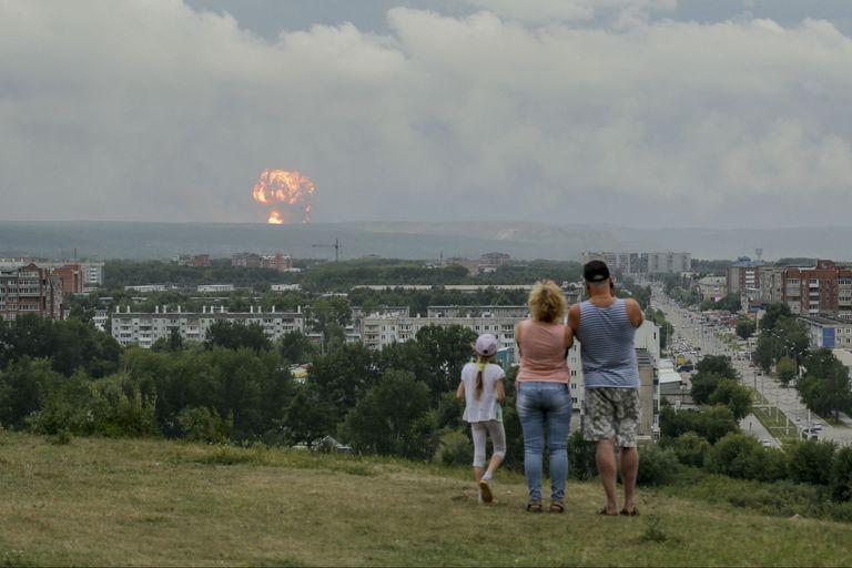 En esta foto tomada el lunes 5 de agosto de 2019, una familia observa explosiones en un depósito militar de municiones cerca de la ciudad de Achinsk, en la región de Krasnoyarsk, en el este de Siberia