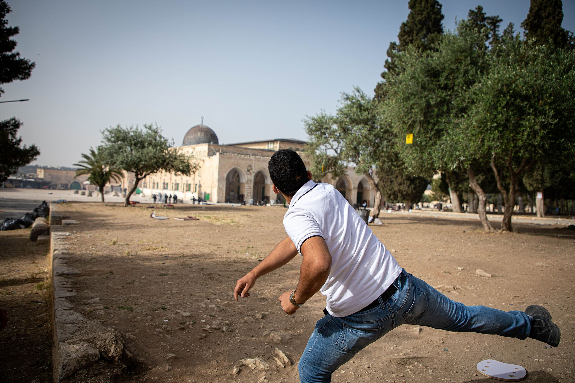 Un palestino lanza una piedra contra la policía israelí que utiliza gas lacrimógeno, balas de goma y granadas de aturdimiento para dispersar manifestantes palestinos que custodiaban la Mezquita de Al-Aqsa, Jerusalén
