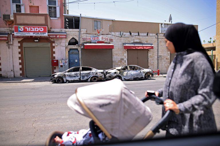 Una mujer árabe israelí observa autos quemados en la ciudad central israelí de Lod