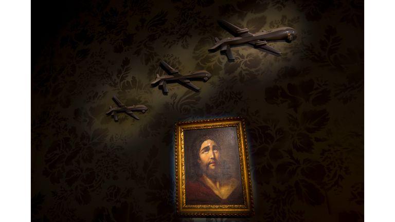 Una pared decorada con modelos de drones y una pintura de Jesús con un punto de un francotirador en su frente