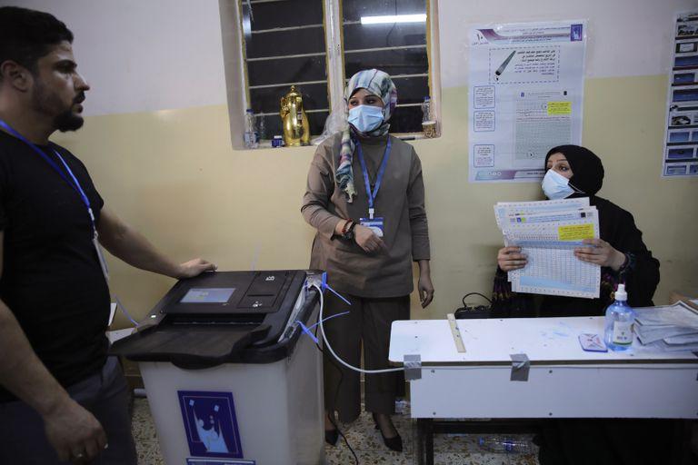 Una mujer iraquí muestra su dedo manchado de tinta tras votar en un centro electoral en las elecciones parlamentarias en Bagdad, Irak, el domingo 10 de octubre de 2021. (AP Foto/Hadi Mizban)