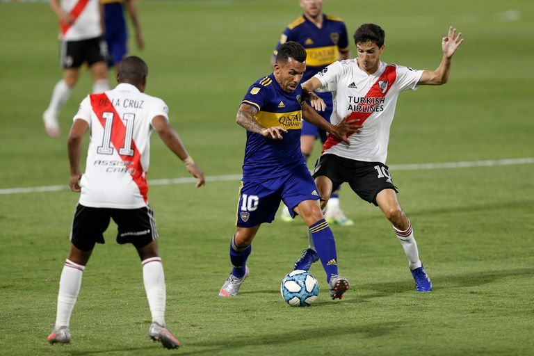Carlos Tevez se lleva la pelota ante la marca de Nacho Fernández; el 10 de Boca ingresó y aportó su cuota ofensiva