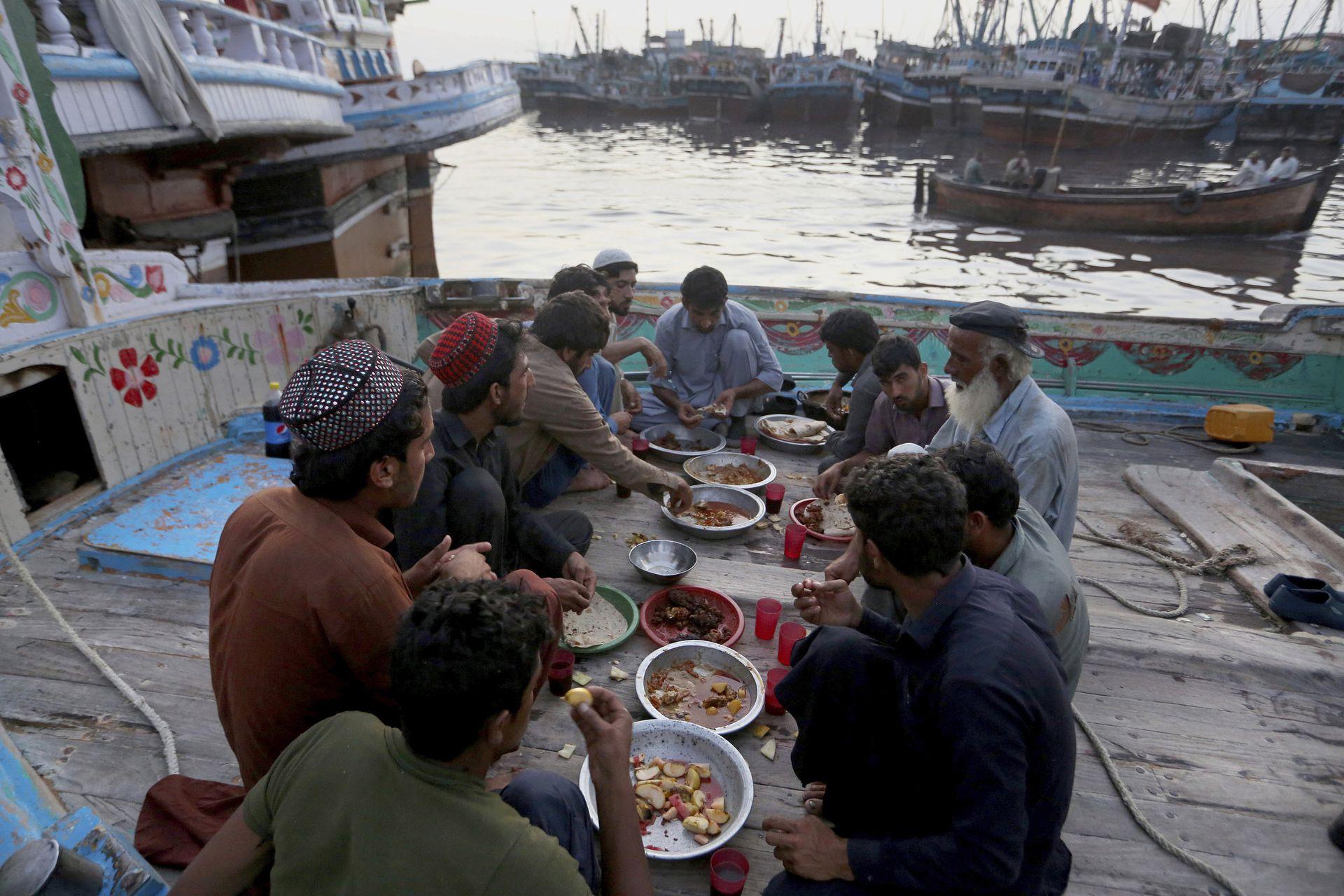Pescadores rompen su ayuno dentro de un barco, en un astillero ubicado en Karachi, Pakistán, el martes 20 de abril de 2021