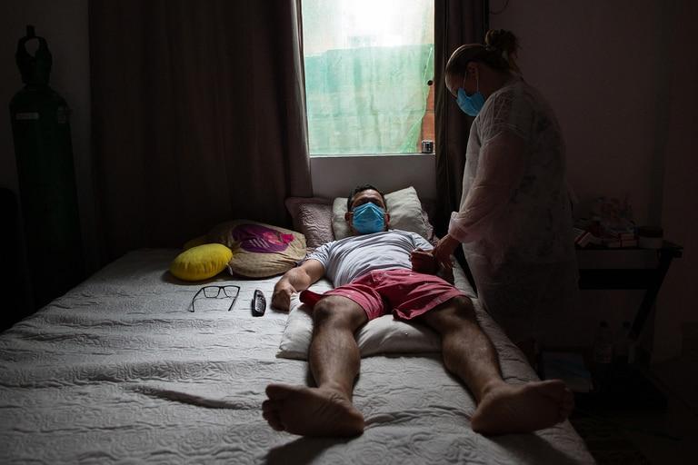 La enfermera Marcicleia Gomes cuida a su hermano, el técnico de enfermería Marcio Moraes, de 43 años, quien está infectado con Covid-19, en su casa de Manaus, Brasil, el 28 de enero de 2021