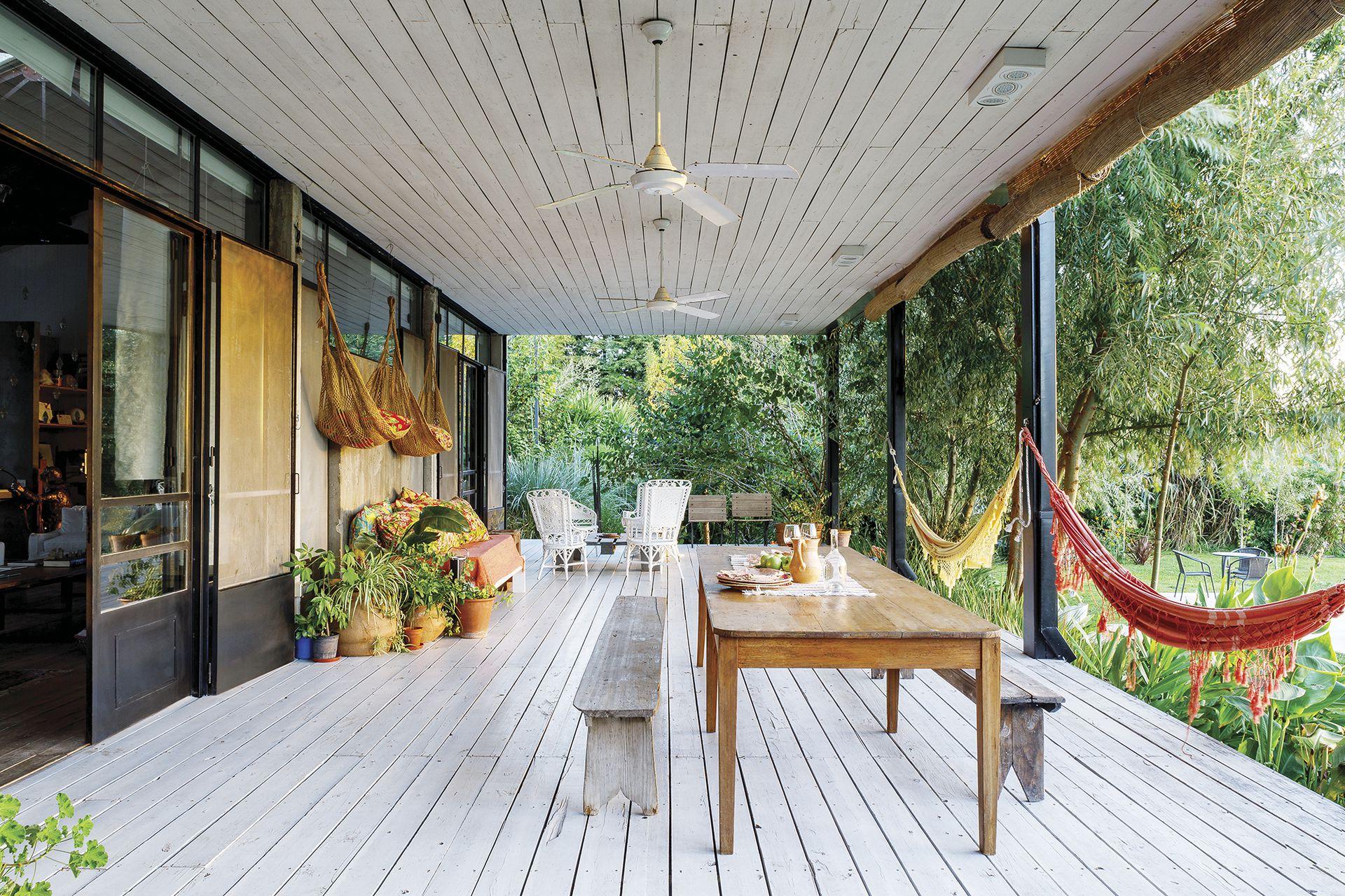 En la galería, mesa y banco de madera, dos hallazgos de Berna en una compraventa de la zona. Hamacas traídas de Brasil y ventiladores de techo (Martin & Martin).
