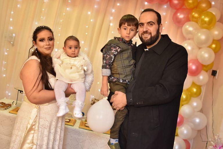El sacerdote siriano ortodoxo Jorge Bahnam, junto a su esposa Suha y sus dos pequeños hijos durante la fiesta de bautismo de la pequeña