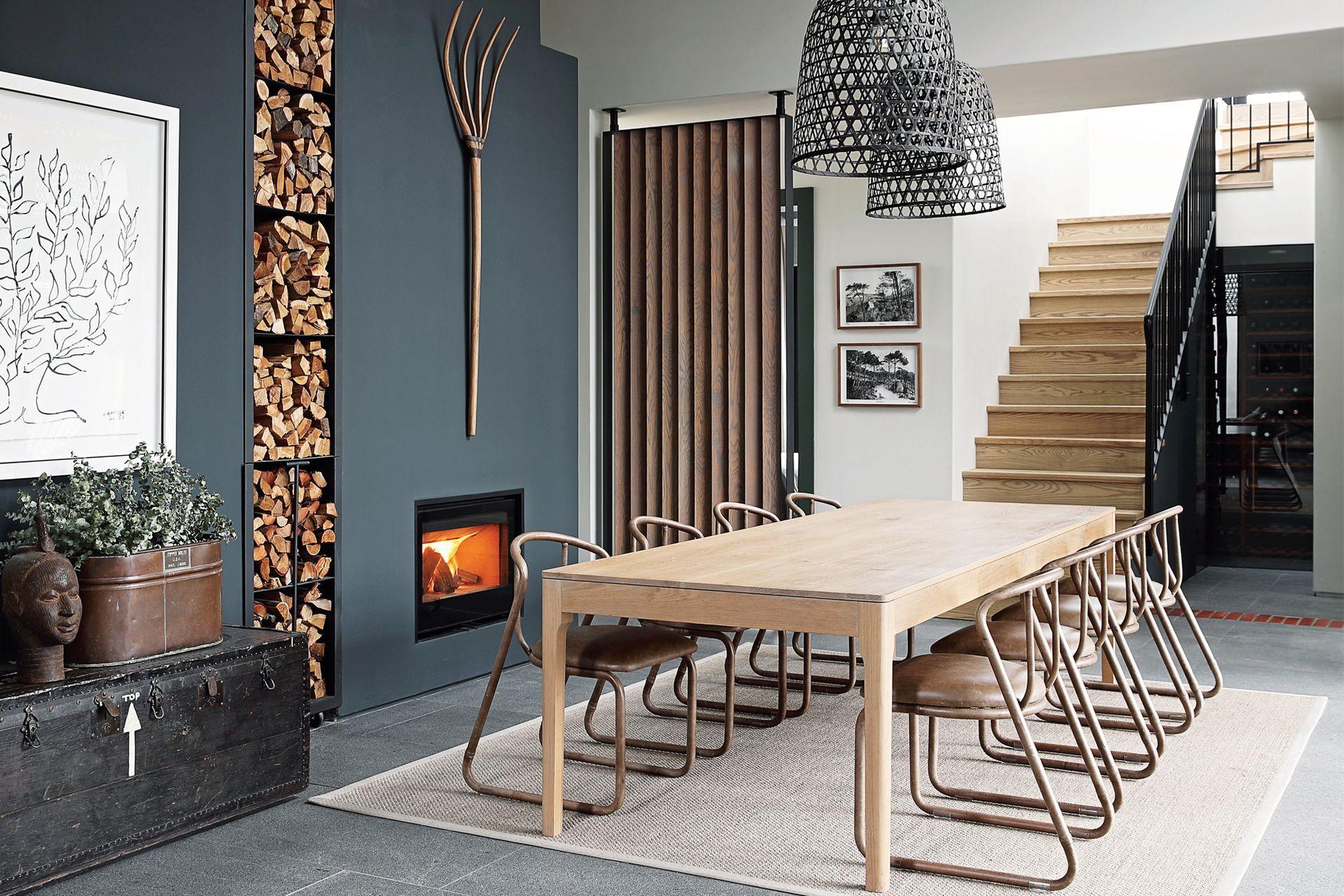 Chimenea (Charnwood). Mesa 'Harris' (James Mudge). Sillas de acero tubular con asiento tapizado en cuero (Studio 19). Lámparas colgantes (Loft Living).