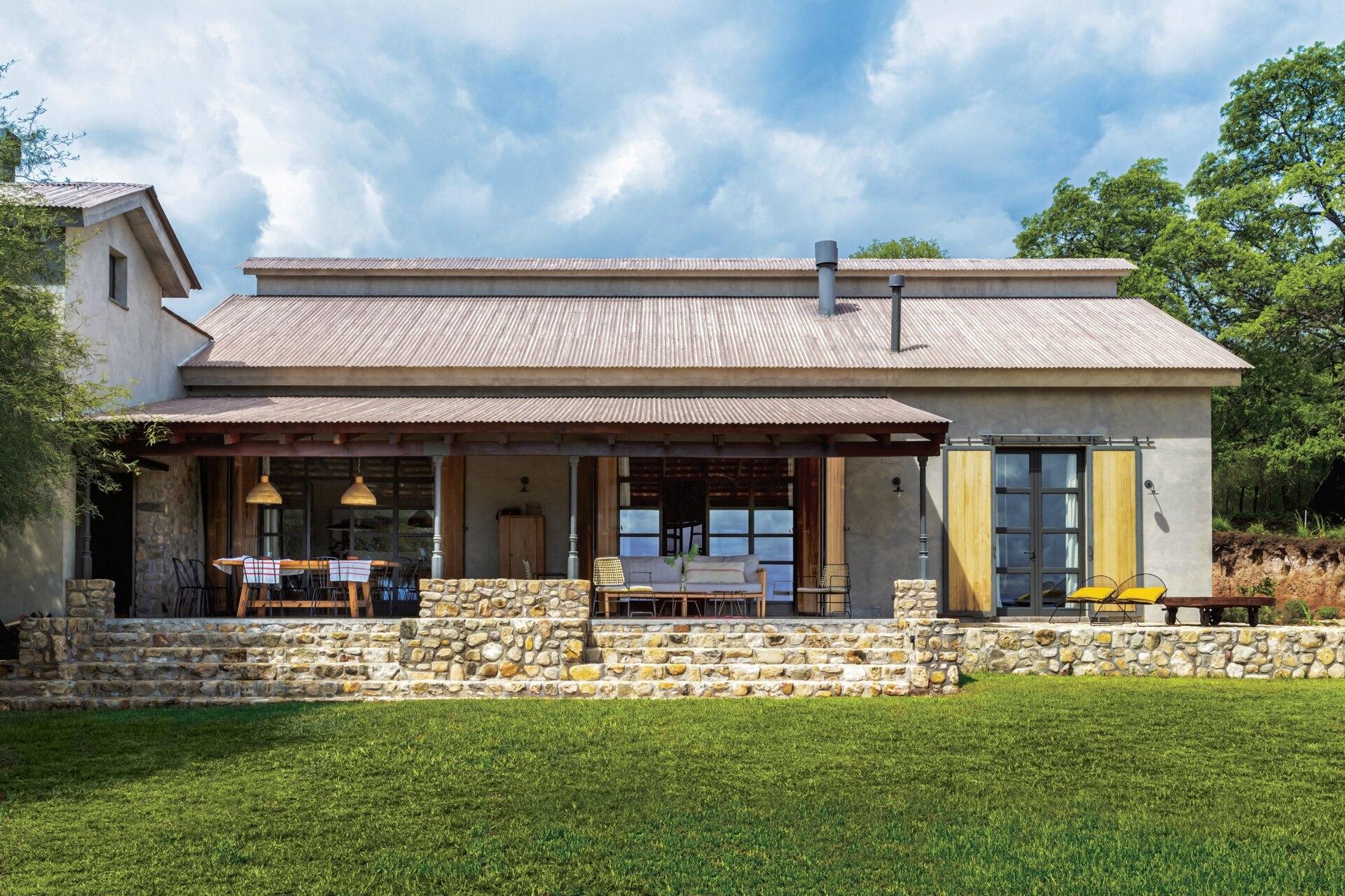 Vista de la casa en la que se aprecia el basamento hecho con piedra del lugar y los techos con chapas tratadas para dar un efecto añejo.